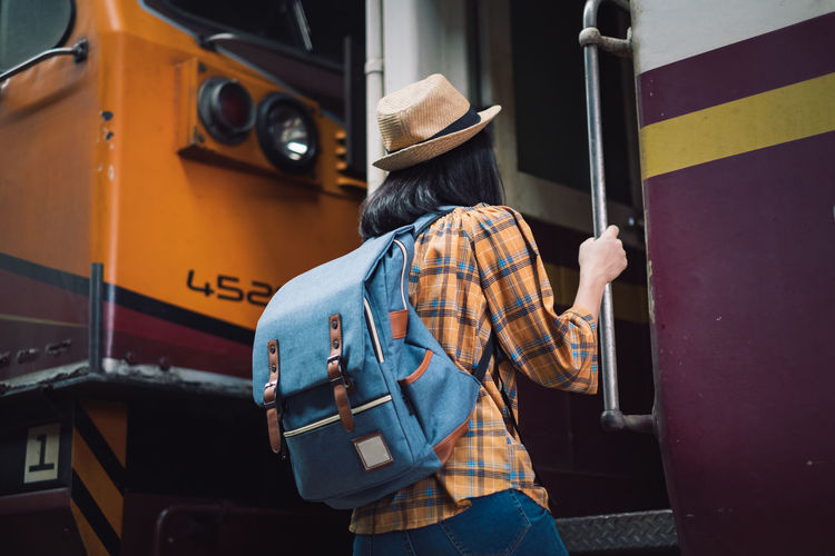 Rear view of man standing by train
