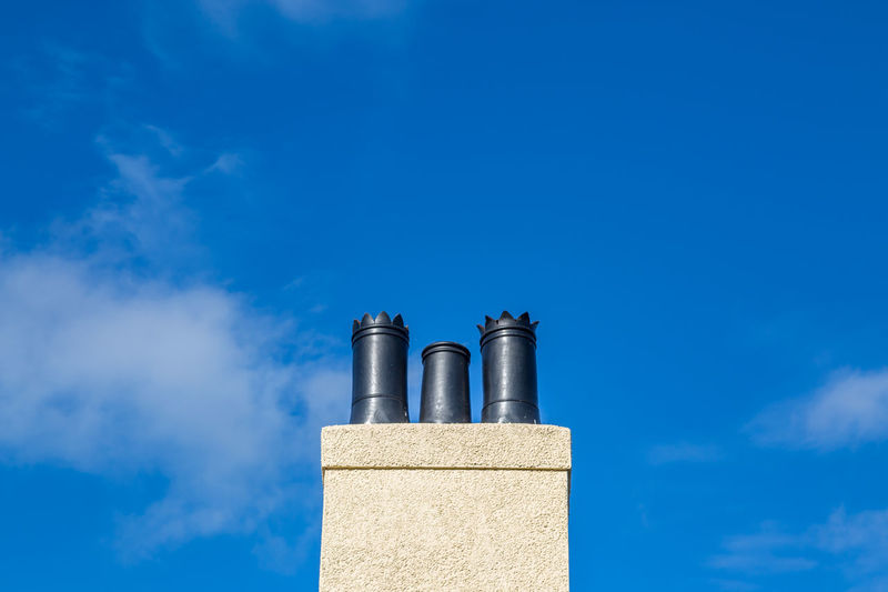Looking up at a decorative chimney stack against a blue sky Architecture Blue Building Exterior Built Structure Chimney Chimney Pots Chimney Stacks Close-up Cloud - Sky Copy Space Day Equipment Low Angle View Metal Nature No People Outdoors Sky Sunlight