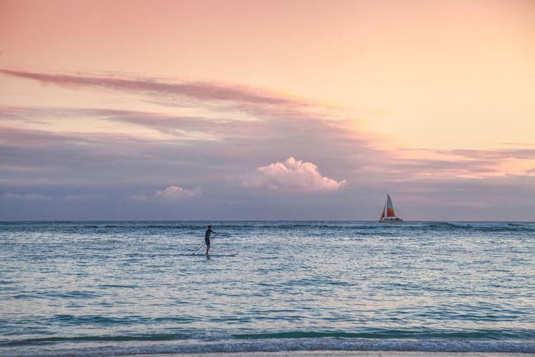 Man paddleboarding on sea against sky during sunset