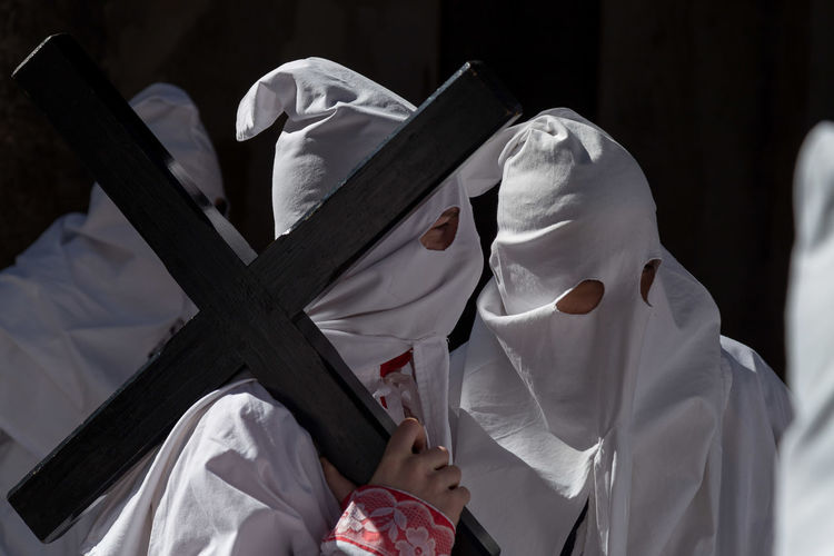 Penitentes holding cross while standing on street