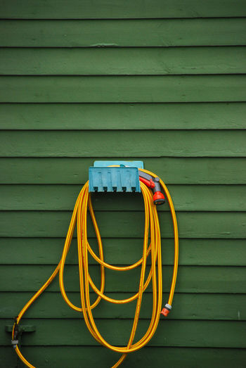 Garden hose hanging on green wall at yard