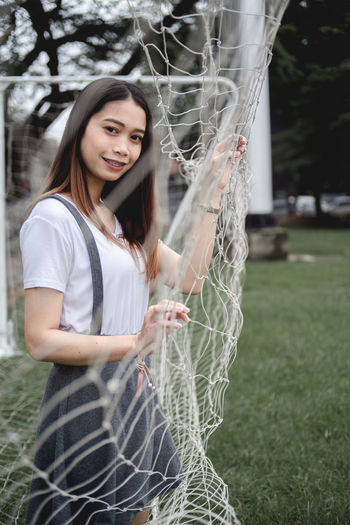 Portrait of smiling young woman standing in goal post