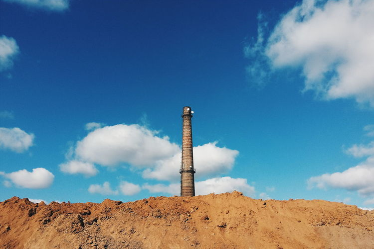 Low angle view of abandoned smoke stack on industrial site against sky