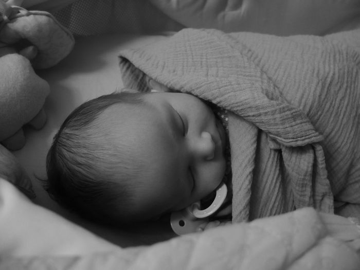 Close-Up Of Baby Wrapped In Blanket