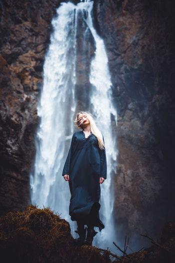 Young woman looking at waterfall