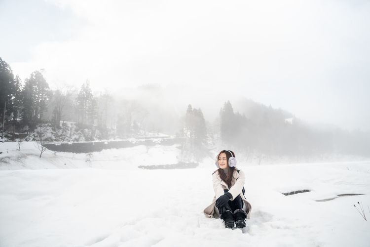 One Person Winter Snow Cold Temperature Full Length Sitting Nature Young Adult Day Adult Beauty In Nature Warm Clothing Leisure Activity White Color Clothing Mountain Real People Outdoors Extreme Weather