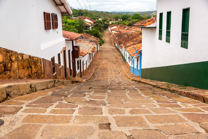 Looking down a beautiful colonial street in Barichara, Colombia Architecture Barichara Building Colombia Colonial Culture Exterior Faith Façade Historic Historical House Landmark Old Sandstone Santander Spanish Stone Street Tourism Town Travel Typical Vacation White