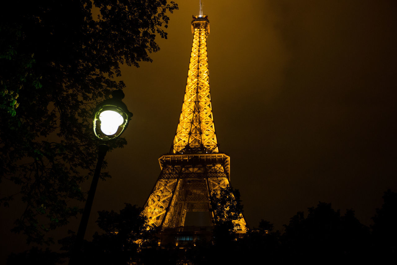 architecture, illuminated, low angle view, tower, built structure, travel destinations, tourism, lighting equipment, metal, night, outdoors, no people, monument, travel, gold colored, statue, sky, sculpture, tree, building exterior, city