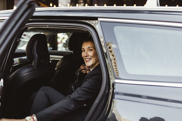 Portrait of a smiling young woman sitting on car