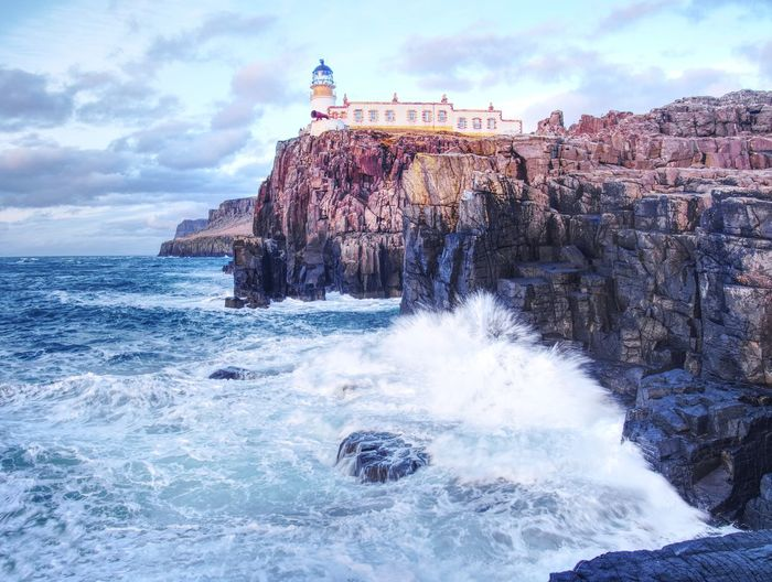 Famous view to neist point lighthouse on end of world. foamy evening blue sea strikes against cliff