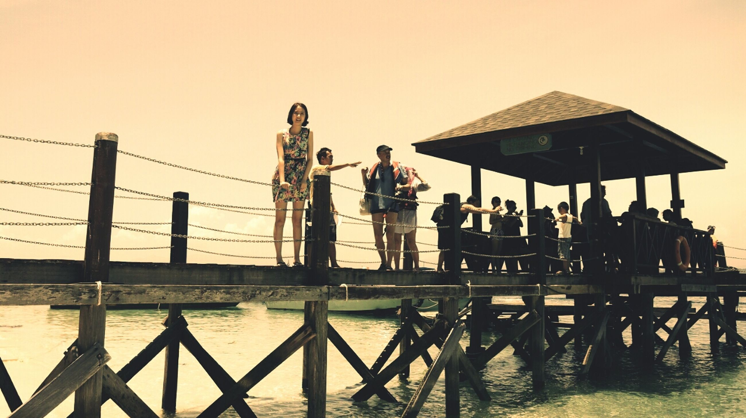 water, sea, men, clear sky, leisure activity, lifestyles, built structure, railing, person, pier, architecture, large group of people, sky, copy space, medium group of people, standing, togetherness, outdoors