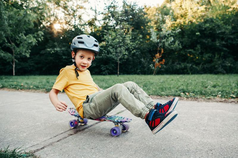 Happy caucasian boy in grey helmet riding skateboard on road in park on summer day. outdoor activity