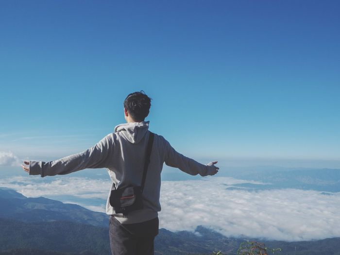 Man with arms outstretched standing against blue sky