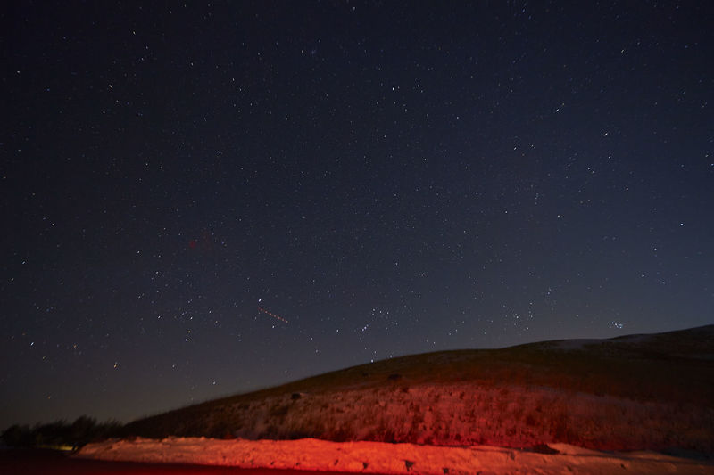 Low angle view of hill against star field sky during night