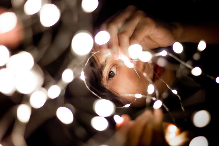 Close-up of woman with illuminated string light