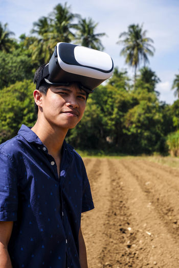 Portrait of man wearing virtual reality simulator while standing on field against sky