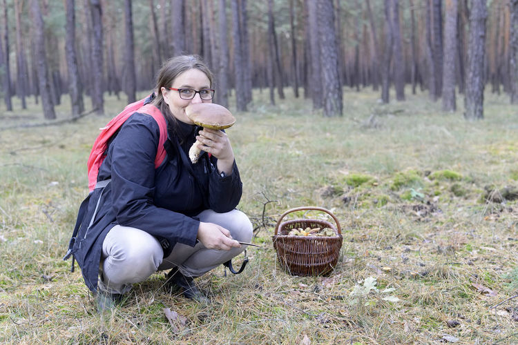 woman picking mushrooms Autumn Collecting Finding Happy Mushrooms Woman Aroma Basket Flavour Forest Lifestyles Mushroomer Nature One Person Outdoors Picking Searching Sitting Smelling Smiling Successfully