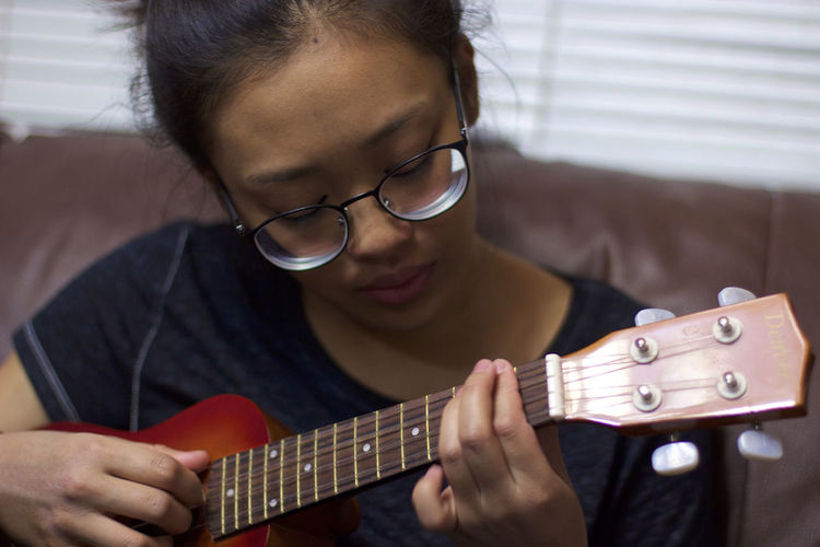 Teenage girl playing ukulele at home