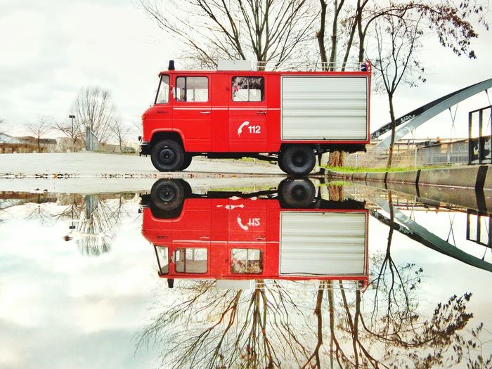 Reflection of red fire engine in puddle on street