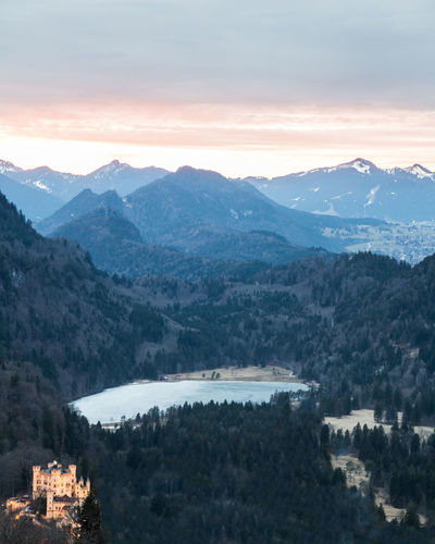 The castle 'Hohenschwangau' in Bavaria in front of an epic landscape. The castle looks kind of photoshopped into the picture. That's because it's illuminated in the evening and the rest of the landscape of course not ;) Alps Architecture Astronomy Bavaria Beauty In Nature Building Exterior Castle Fog Frozen High Angle View Hohenschwangau Landscape Mountain Mountain Peak Mountain Range Nature Nature Night No People Outdoors Scenics Sky Star - Space Sunset Travel Destinations