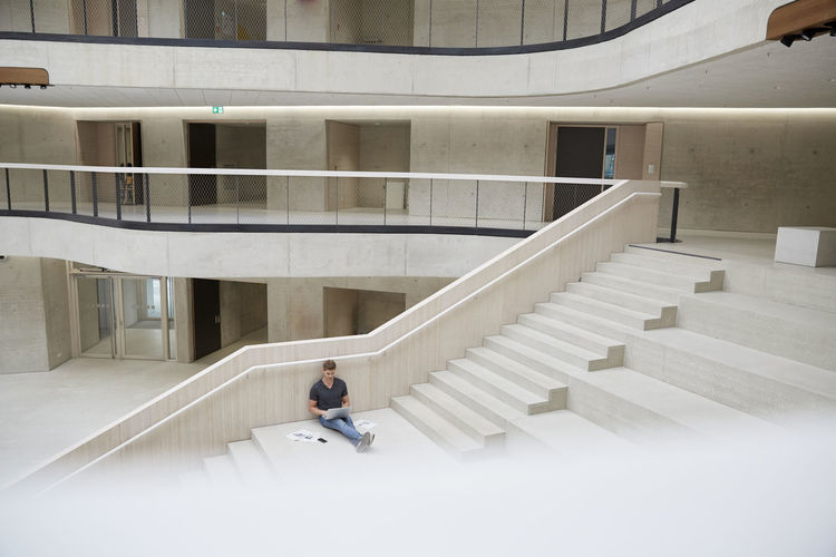 Man sitting on staircase of building