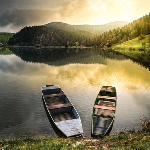 Two old boats at a coast of a lake reflecting warm light of rising sun (Dedinky village at Palcmanska Masa water reservoir, Slovakia) Beauty In Nature Day Grass Lake Landscape Moored Mountain Nature Nautical Vessel No People Outdoors Reflection Scenics Sky Tranquil Scene Tranquility Travel Destinations Tree Water The Great Outdoors - 2017 EyeEm Awards
