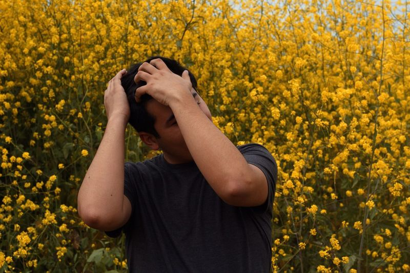 Young man with hands in hair standing against yellow flowering plants at farm