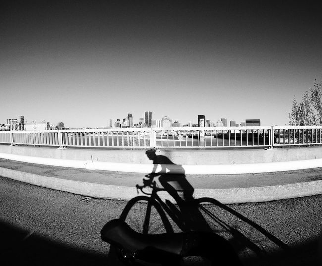 Man riding bicycle on city against clear sky