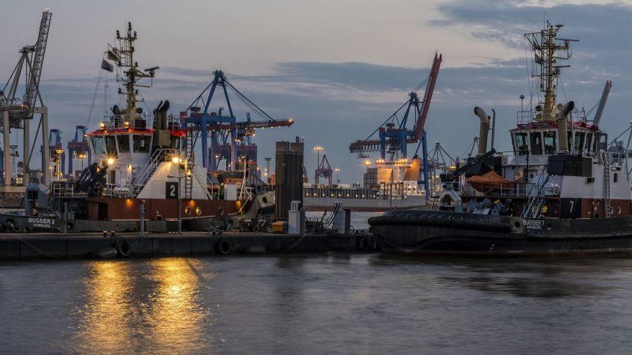 Tugboats in elbe river at illuminated harbor