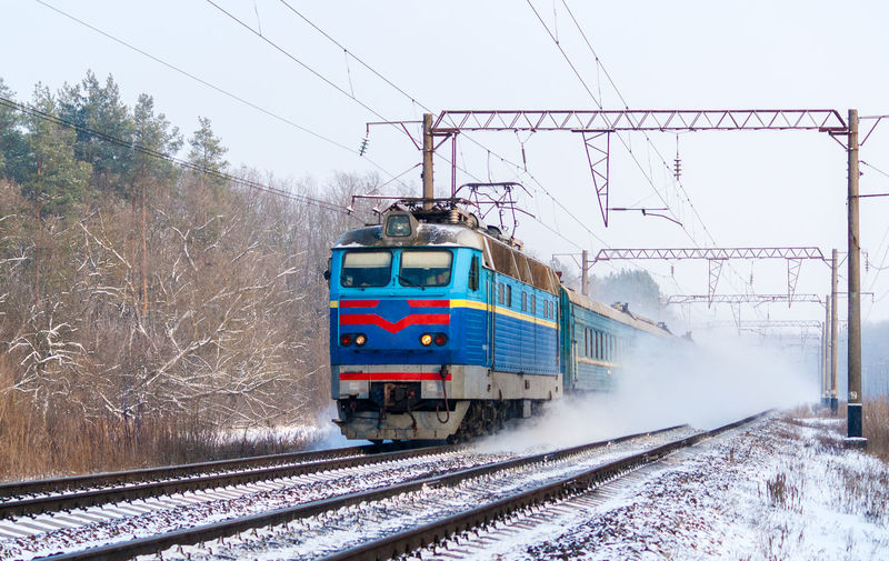 Train on railroad tracks against sky during winter