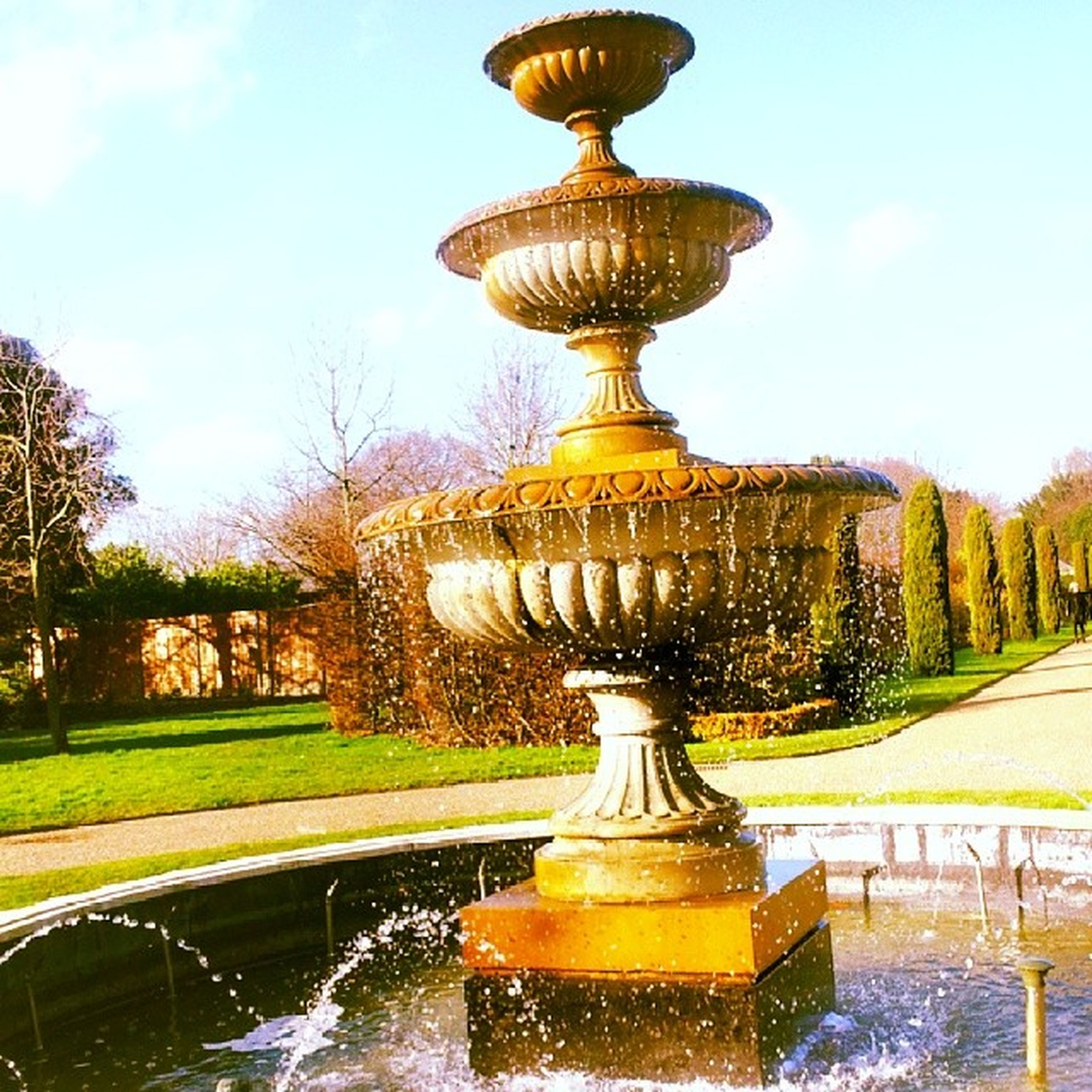 fountain, architecture, built structure, statue, art and craft, building exterior, tree, water, art, sculpture, sky, creativity, human representation, dome, reflection, travel destinations, pond, famous place, religion, park - man made space
