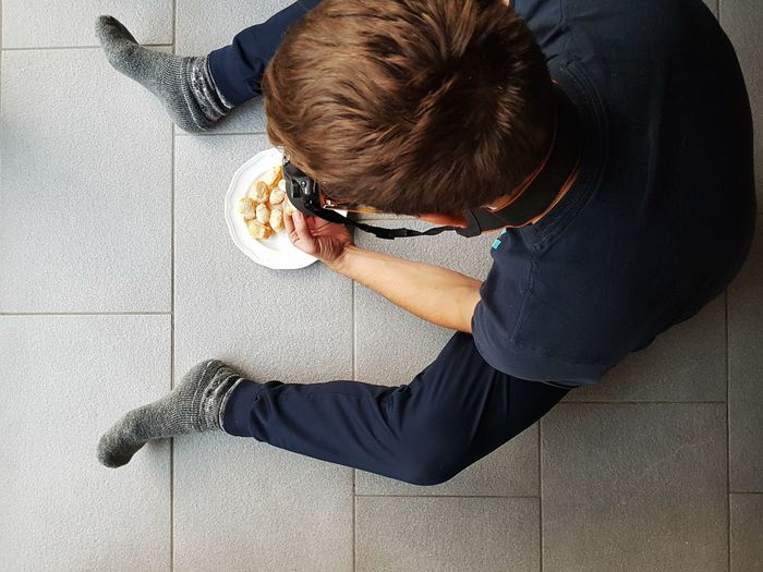 High angle view of man sitting on tiled floor