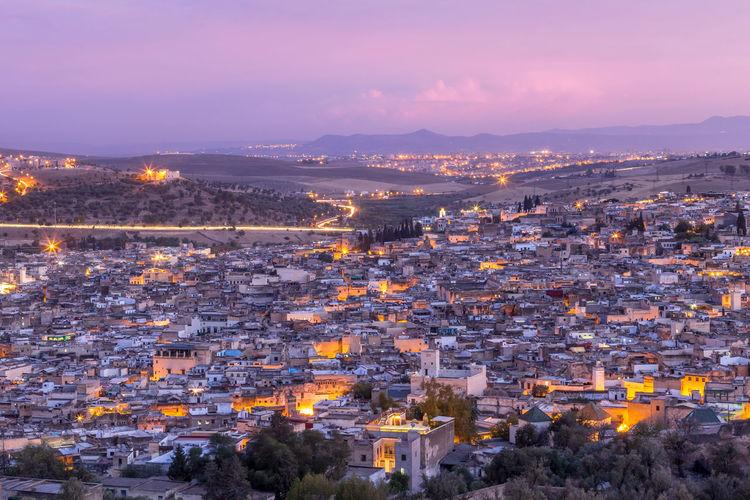 High Angle Shot Of Illuminated Cityscape Against Sky At Sunset