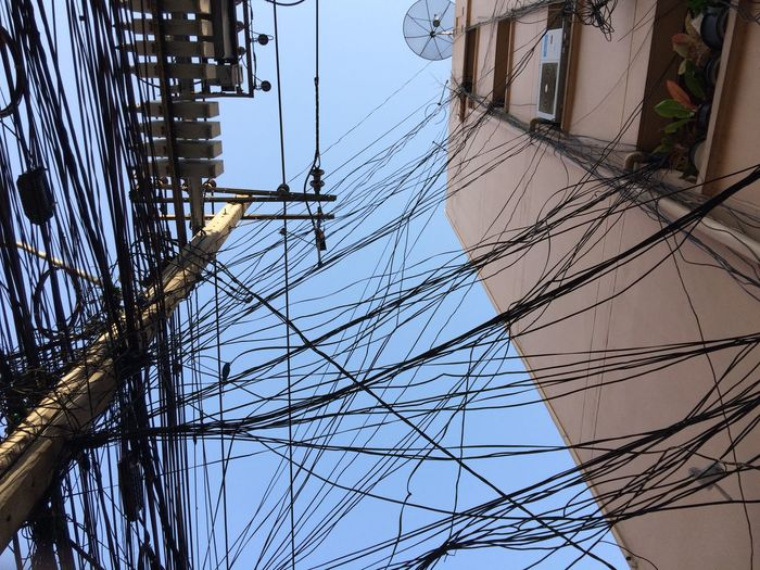 Low Angle View Of Power Lines Against House