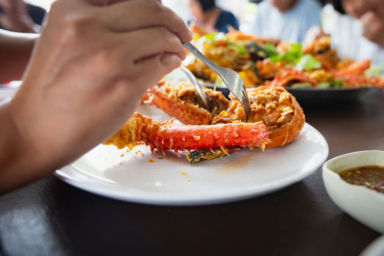 Woman hand holding fork dipping in piece of fried lobster shrimp with garlic on the plate.