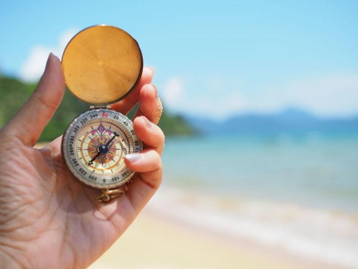 Close-up of woman holding navigational compass at beach