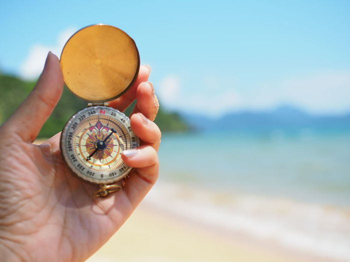 Close-up of hand holding compass at beach against sky