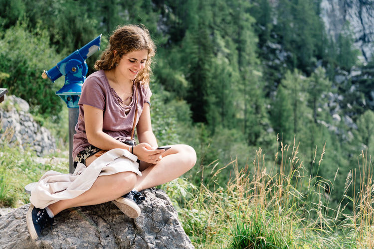 Beautiful young woman sitting texting on smartphone in nature Nature Sitting Adult Adventure Beautiful Woman Beauty Beauty In Nature Blond Hair Casual Clothing Curly Hair Day Forest Full Length Girl Grass Happiness Hiking Lifestyles Nature One Person One Young Woman Only Outdoors People PhonePhotography Real People Sitting Smartphone Smiling Texting Tree Young Adult Young Women