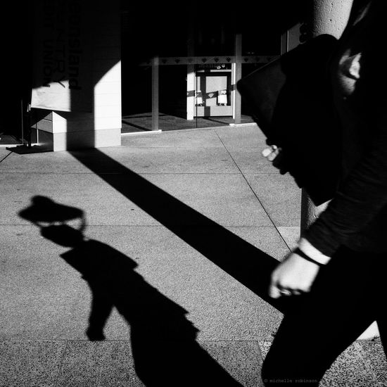 Shadow of man on woman in city