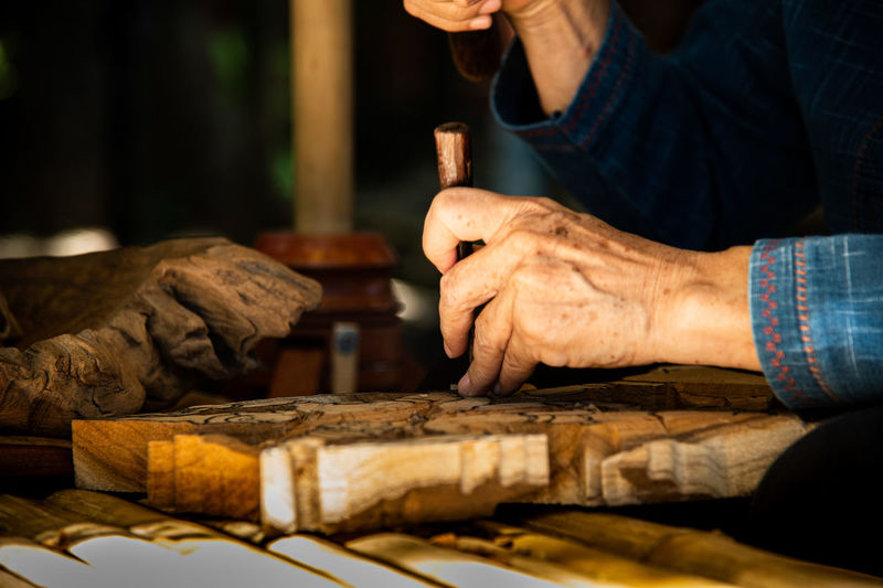 Midsection of man carving wood at table in workshop