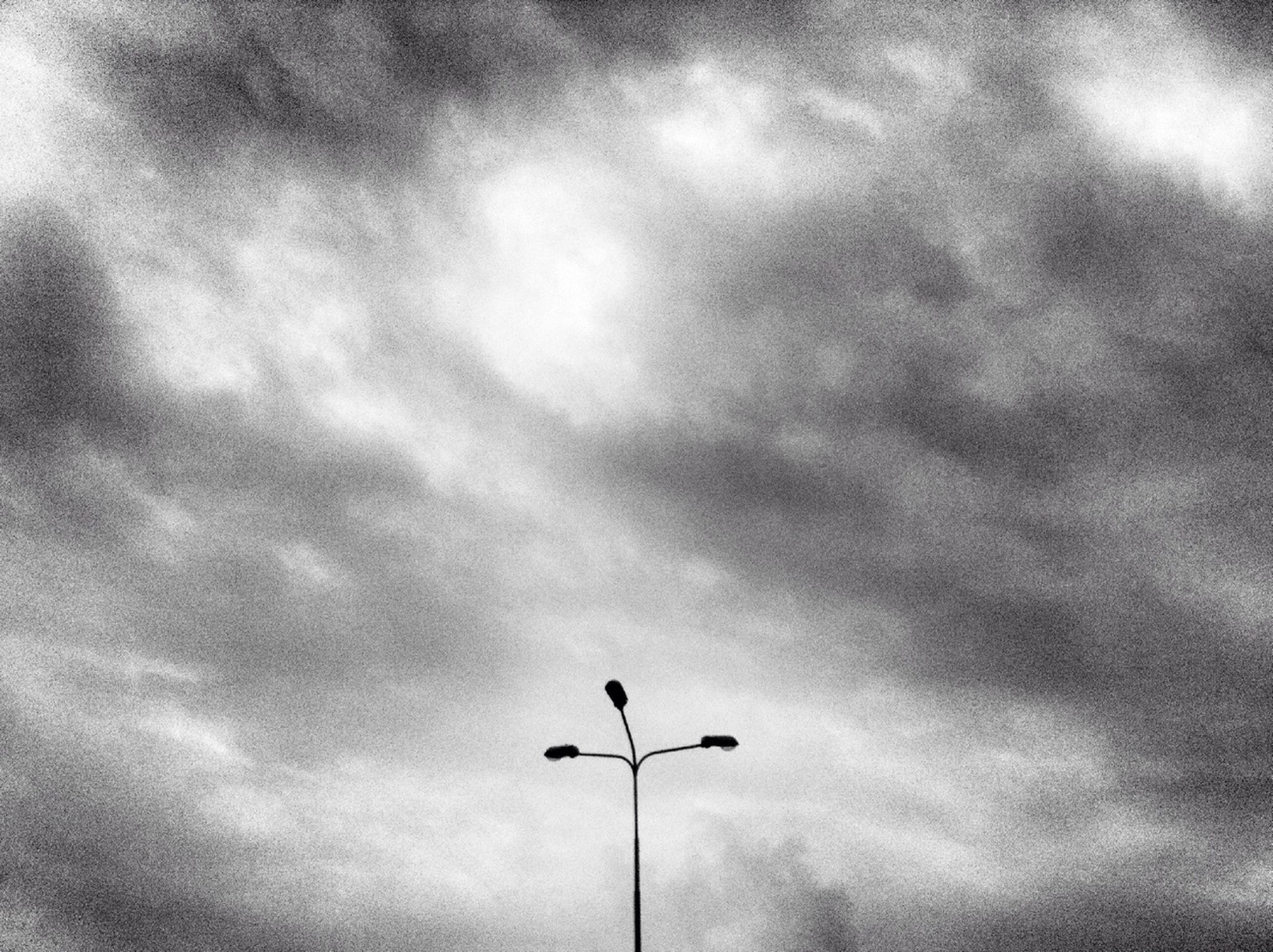 low angle view, sky, street light, cloud - sky, cloudy, lighting equipment, silhouette, cloud, overcast, high section, outdoors, nature, weather, pole, no people, dusk, day, electricity, tranquility, beauty in nature