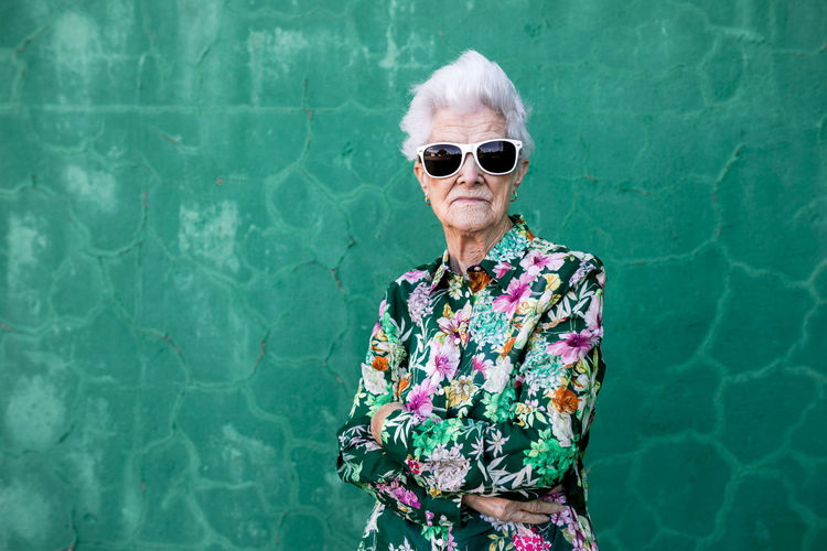 Portrait of woman wearing sunglasses standing against wall