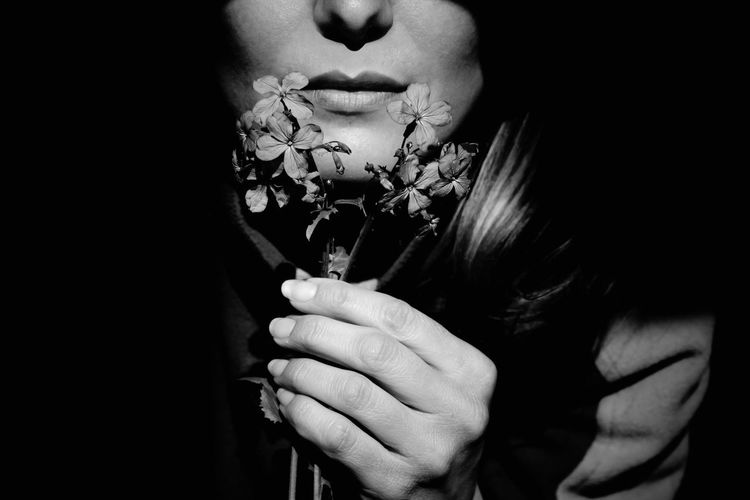 Close-up of woman holding pink flower against black background