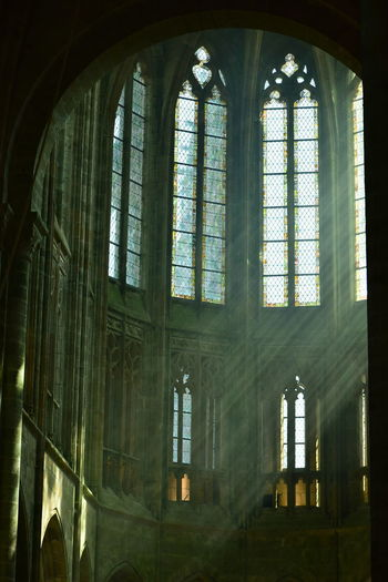 Haze in the church at Le Mont Saint Michel, France Arch Architecture Belief Building Built Structure Day Glass Glass - Material Indoors  Low Angle View No People Place Of Worship Religion Spirituality Stained Glass Transparent Window