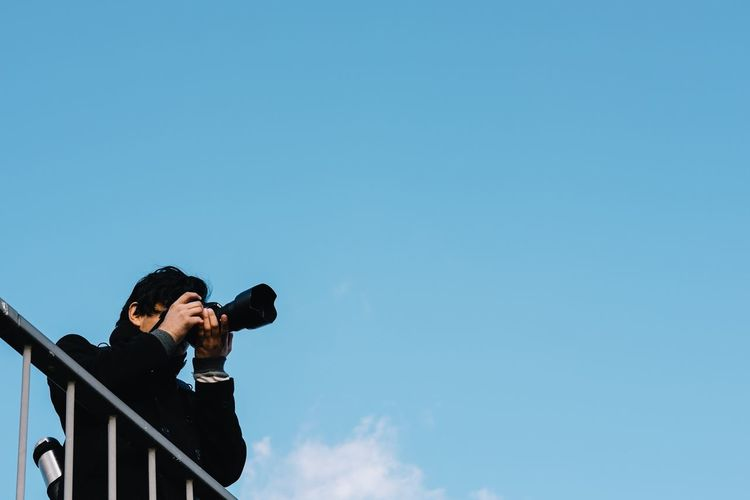 Man photographing against sky on sunny day