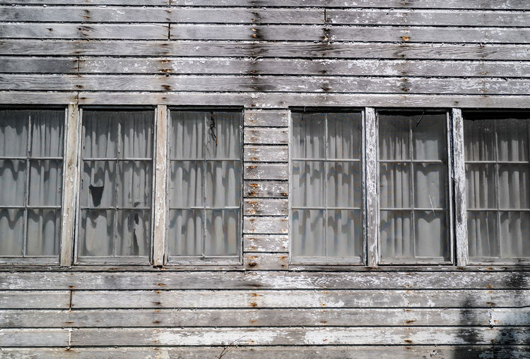Windows of abandoned and weathered wood house