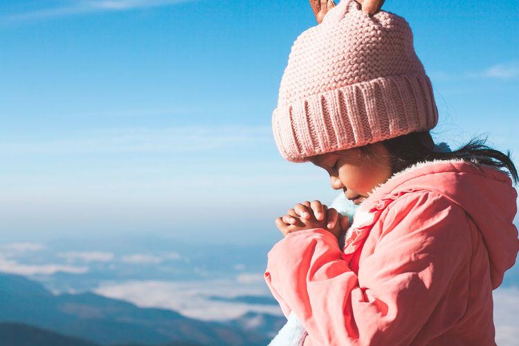 Cute girl praying against sky