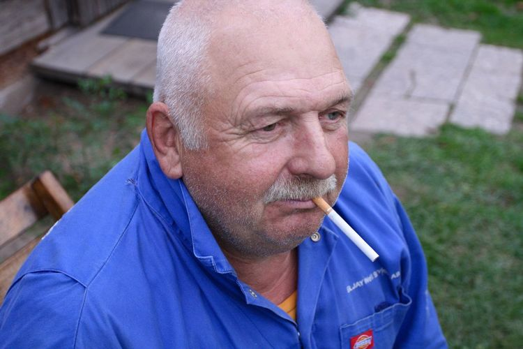 High Angle View Of Mature Man Smoking Cigarette While Sitting Outdoors