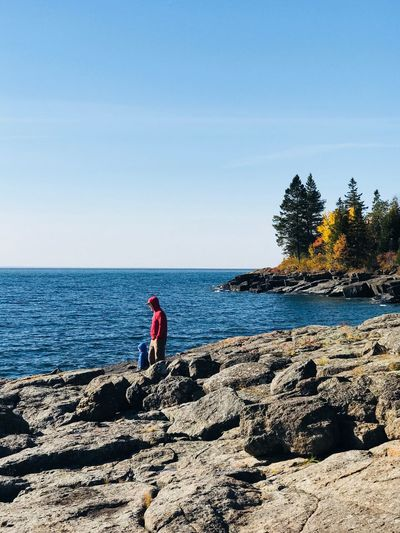 Man and young boy standing on the rocky shore of Lake Superior in the fall. Sea Horizon Over Water Rock - Object Nature Water Two People Clear Sky Scenics Tranquil Scene Beauty In Nature Full Length Day Tranquility Real People Outdoors Sky Beach Standing Lifestyles Vacations Fatherhood Moments Father & Son Autumn Cool Weather Cold