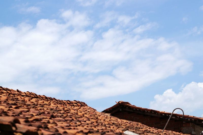 Low angle view of roofs against sky
